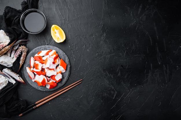 Krabbenstangen halbfertiges fischhackfleisch mit meeresfrüchten und blauem schwimmkrabbenset, auf steinbrett, auf schwarzem hintergrund, draufsicht flach, mit copyspace und platz für text