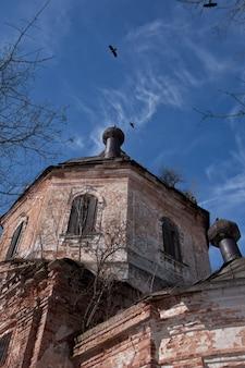 Krähen und wolken am himmel über alter zerstörter kirche im russischen land