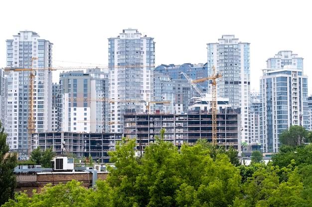 Kräne auf einer baustelle des gebäudes des modernen wohnviertels hohe mehrfamilienhäuser oder wolkenkratzer in einem neuen elite-komplex.