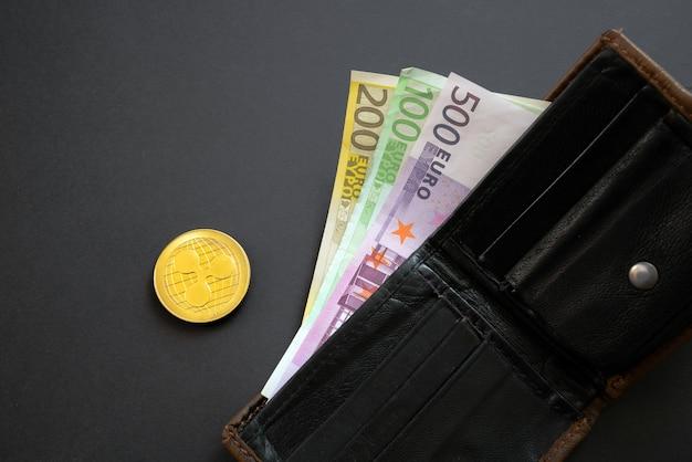 Kräuseln sie die münze neben den euro-banknoten, die aus einer brieftasche auf der schwarzen oberfläche herausragen.
