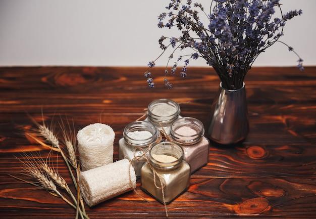 Kräuter-bio-ubtan in glasflasche auf hölzernem hintergrund mit getrockneten lavendelblüten