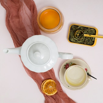 Kräuter; getrocknete zitronenscheiben; teekanne; honigglas mit braunem textilstoff über dem konkreten hintergrund