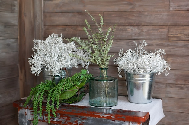 Kräuter, grüne zweige des eukalyptus in einem vase auf einem holztisch. das cottage ist modern mit holzwänden und möbeln eingerichtet. rustikales interieur. skandinavien. wohnzimmer im landhausstil