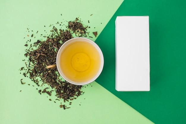 Kräuter mit grünem tee und weißer kasten auf grünem hintergrund