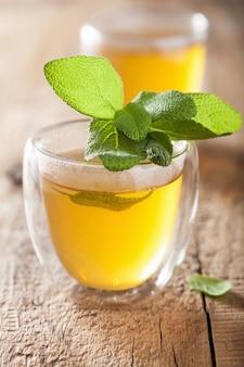 Kräuter-salbei-tee mit grünem blatt in der glasschale