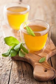 Kräuter-salbei-tee mit grünen blättern in glasbechern