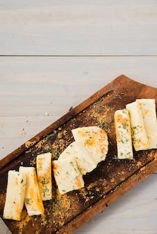 Kräuter und gewürze auf käsescheiben über dem holztisch