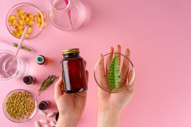 Kräuter und kräuter-nahrungsergänzungsmittel draufsicht auf rosa hintergrund