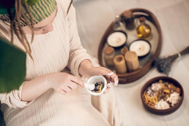 Kräuter und öle. weibliche ayurvedische therapeutin, die in einem garten sitzt und medizin vorbereitet