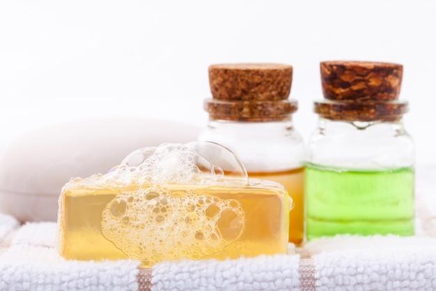 Kräuterbadekursseife auf weißem badtuch mit honigisolat auf weißem hintergrund.