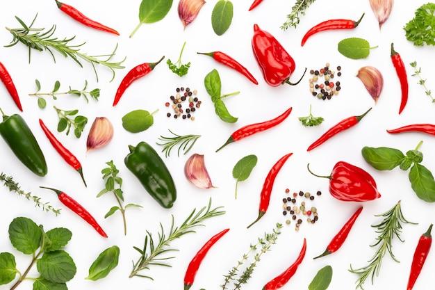 Kräuterblätter und chili auf weißem tisch würzen