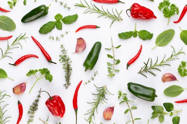 Kräuterblätter und chili auf weißer oberfläche würzen. gemüsemuster. blumen und gemüse auf weißer oberfläche. draufsicht, flach liegen.