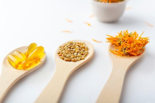 Kräuterkapsel, natürliche vitamine, trockene ringelblumenblumen am hölzernen löffel auf weißem hintergrund. konzept der gesundheitsversorgung und alternativmedizin: homöopathie und naturheilkunde.