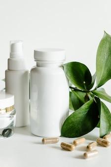Kräuterkapseln und weiße flaschen, gesundheits- und schönheitskonzept.