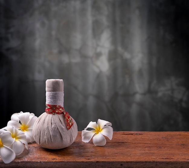 Kräuterkompressenmassage auf holztisch im dunklen hintergrund thailändisches spa- und massagekonzept