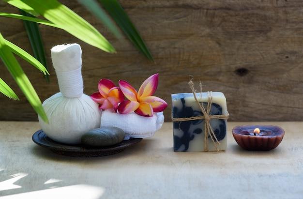 Kräutermassageball und indigo-seifen-spa-aromatherapieprodukte auf holztisch