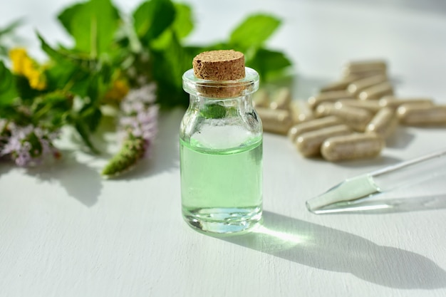 Kräutermedizin, homöopathiekonzept, frische kräuter, pillen, kleine flasche mit extrakt.