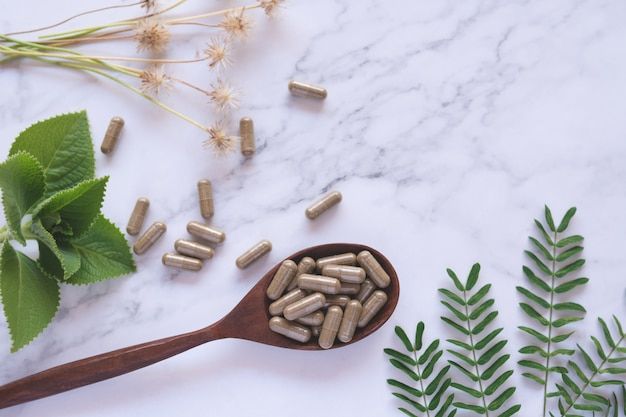 Kräutermedizin in kapseln auf hölzernem löffel mit natürlichem grünem blatt auf weißem marmor