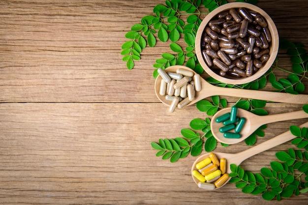 Kräutermedizinergänzung von natürlichem auf holztischhintergrund und kopienraum