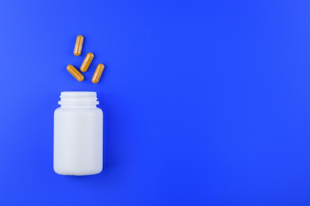 Kräutermedizinkapsel und weiße flasche auf blauem hintergrund, medizin und droge.