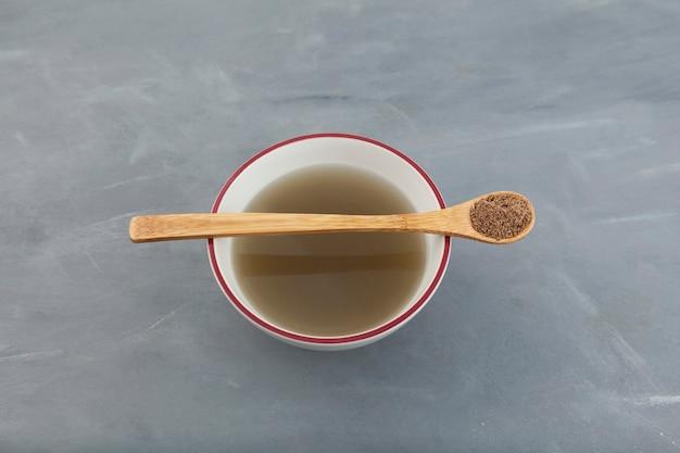 Kräutertee aus natürlichem mariendistelpulver oder silybum marianum extrakt auf grau