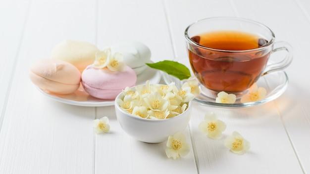Kräutertee, eine schüssel marshmallows und jasminblüten auf einem tisch