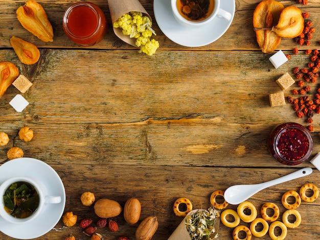Kräutertee, getrocknete früchte und süßigkeiten auf einem alten holztisch. in der mitte des platzes für text.