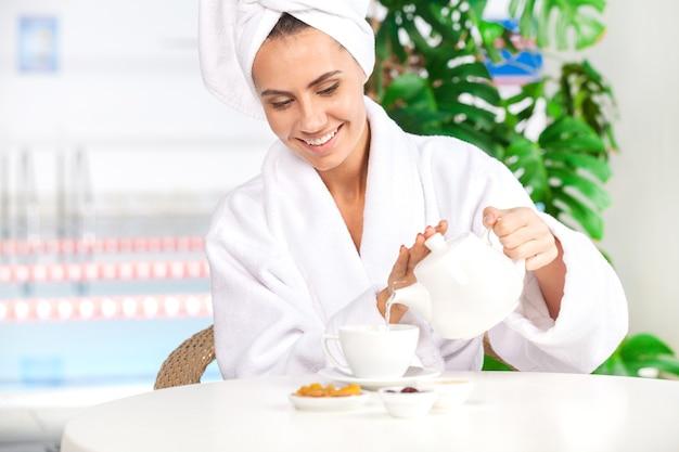Kräutertee gießen. attraktive junge frau im bademantel, die tee in die tasse gießt und lächelt, während sie vor dem schwimmbad sitzt?