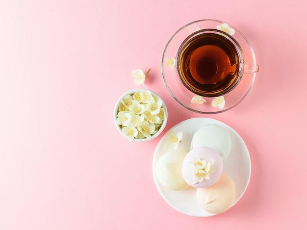 Kräutertee, honig, jasminblüten und ein holzlöffel auf einem rosa schönen tisch