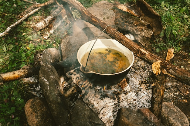 Kräutertee im kessel wird auf lagerfeuer erhitzt, umgeben von aschensteinen in der nähe von grünem gras. kochen unter freiem himmel. aktive erholung im freien. camping in freier wildbahn. lagerfeuer mit rauch.