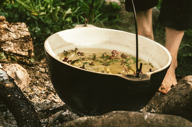Kräutertee im kessel wird auf lagerfeuer erhitzt, umgeben von steinen auf aschehintergrund in der nähe von grünem gras und nackten füßen. kochen unter freiem himmel. aktive erholung im freien. camping in wilder nahaufnahme.