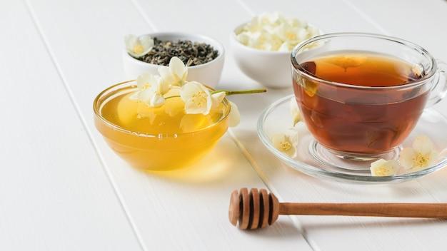 Kräutertee mit jasmin, honig und einem holzlöffel auf einem weißen tisch.
