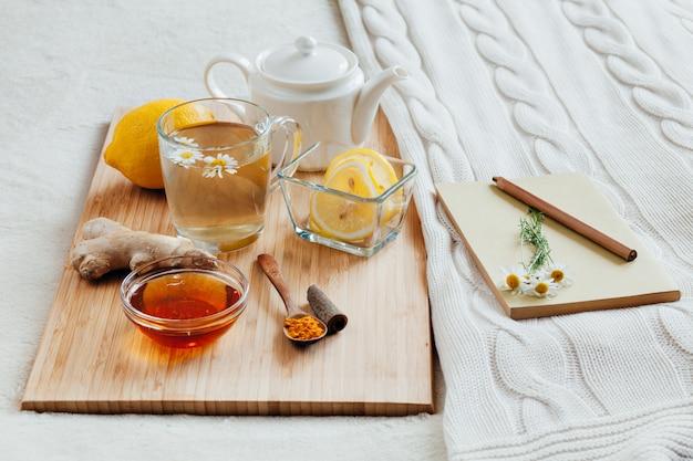 Kräutertee mit kamillenblumen, gelbwurz und honig auf einem hölzernen brett. behandlung von heißgetränk ingwer. volksheilmittel im bett. freizeitbuch.