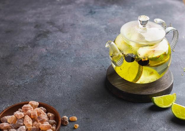 Kräutertee mit limette und bluberry und grünem apfel auf glasteekanne mit braunem zucker
