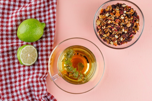 Kräutertee mit limetten, getrocknete kräuter in einer glasschale auf rosa und küchentuch, flach liegen.