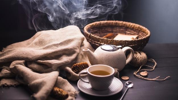 Kräutertee mit tannenzapfen; teekanne; sack; taste; weidenkorb und wollknäuel auf dem tisch