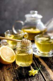 Kräutertee mit zitrone und honig in der glasschale und in der teekanne
