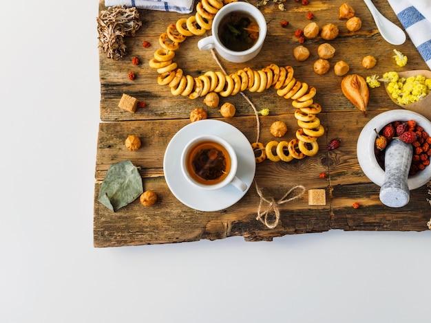 Kräutertee mit zutaten und süßigkeiten auf einem alten brett.