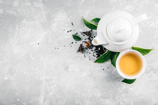 Kräutertee und eine teekanne auf einem konkreten hintergrund