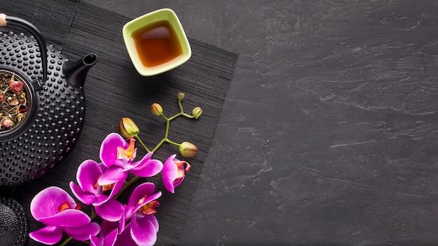 Kräutertee und schöne orchideenblume auf schwarzer platzmatte über schiefersteinhintergrund