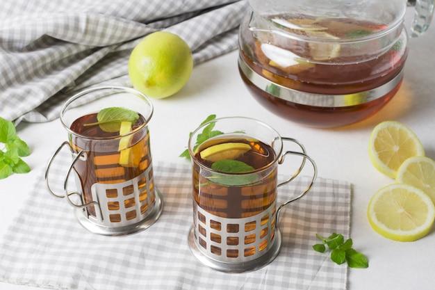 Kräuterzitrone und tadelloser tee auf tischdecke gegen weißen hintergrund