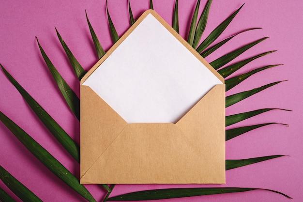 Kraft brauner papierumschlag mit weißer leerer karte auf palmblättern, rosa lila hintergrund, modell leerer buchstabe