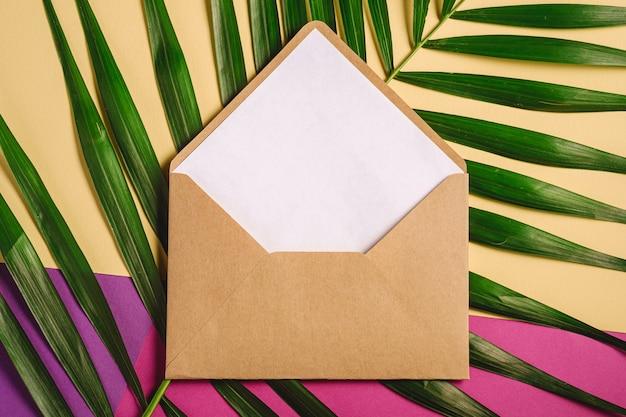 Kraft brauner papierumschlag mit weißer leerer karte auf palmblättern, rosa, lila und cremegelber hintergrund, modell leerer buchstabe