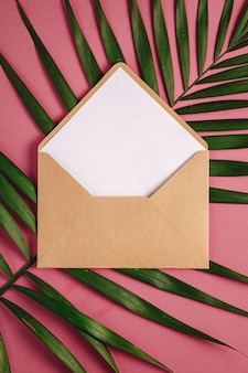 Kraft brauner papierumschlag mit weißer leerer karte auf palmblättern, rosa rotem hintergrund, modell leerer buchstabe