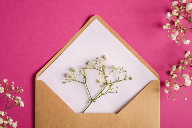 Kraft brauner papierumschlag mit weißer leerer karte, gypsophila-blumen, lila rosa hintergrund