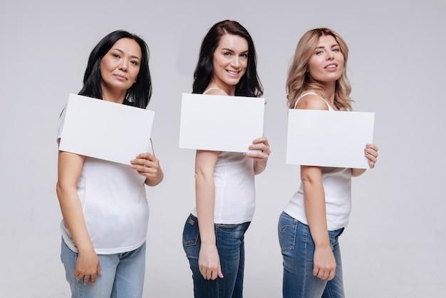 Kraft in vielfalt. wunderschöne stolze, elegante damen, die weiße zettel zeigen und für eine neue soziale kampagne posieren