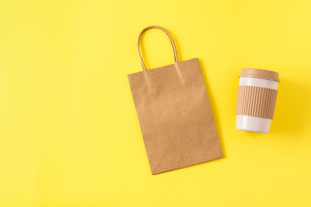 Kraftbeutel mit griffen und wiederverwendbarer tragbarer kaffeetasse auf gelber oberfläche