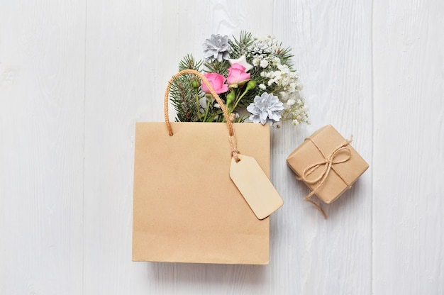 Kraftpaket mit hölzernen tag- und weihnachtsdekortannenzweigen, rosa rosen, kegel
