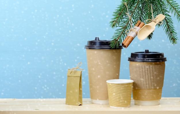 Kraftpapier kaffeetassen und papiertüte auf einem holztisch mit weihnachtsschmuck auf tannenbaum. weihnachtskaffee hintergrund