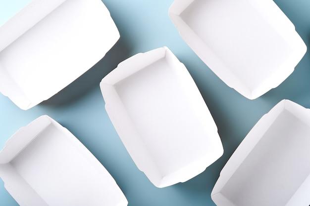 Kraftpapier-lebensmittelbehälter oder teller auf blauem hintergrund. öko-geschirr aus papierhandwerk. recycling- und lebensmittellieferungskonzept. attrappe, lehrmodell, simulation. ansicht von oben, flach.